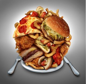 Fast food diet concept served on a plate as a mountain of greasy fried restaurant take out as onion rings burger and hot dogs with fried chicken french fries and pizza as a symbol of compulsive overeating and dieting temptation resulting in unhealthy nutrition.